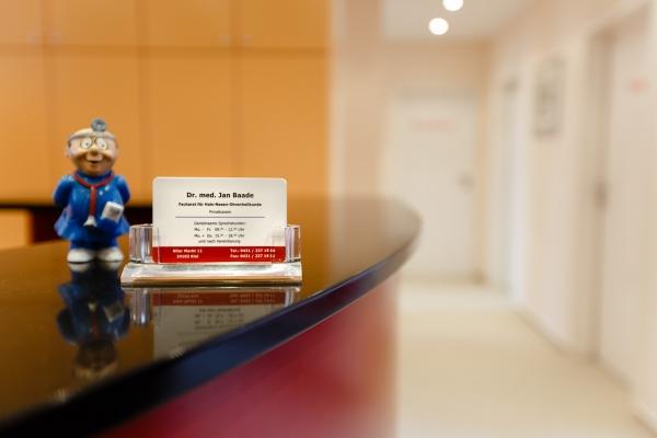 Kleiner Maulwurf im Arztkittel neben Visitenkarten am Empfang HNO Praxis Dr. med Jan Baade